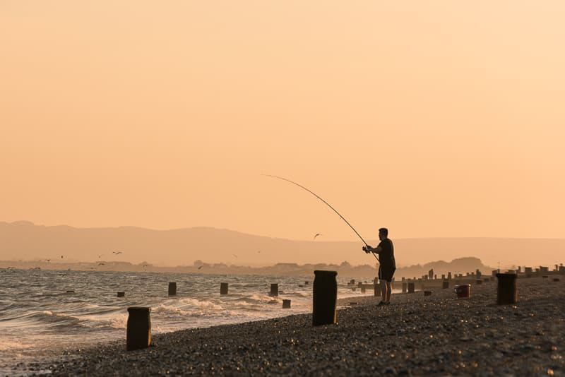 Fisherman at dusk catching mackerel